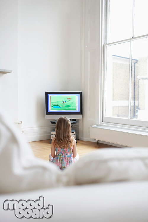 Girl (5-6) watching cartoons in television back view