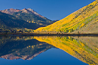 Reflections of Red Mountain and aspen trees in Crystal Lake along the Million Dollar HWY, San Juan Mountains, Colorado.