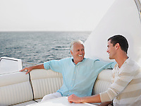 Young and middle-aged man talking on yacht