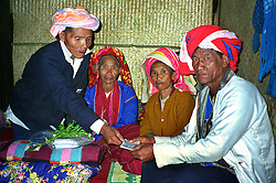BURMA (MYANMAR), Shan State, Peinnebin. 2006. Wan Tha and Ma Ko's parents exchange symbolic gifts before the ceremony. This is a ritual only, as there is no dowry custom among the Palaung.