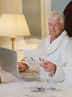 Man sitting in bed using laptop