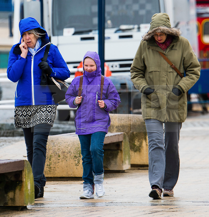 © London News Pictures. 14/04/2017 Aberystwyth, UK.<br /> People on the seafront promenade on a dreary, cold grey and damp Good Friday morning in Aberystwyth on the Cardigan Bay coast of west Wales UK at the start of the Easter Bank Holiday weekend. Photo credit: Keith Morris/LNP