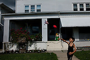 BETHLEHEM, PA – JUNE 14, 2011: Hector Ortiz, age 9, tosses a football to his uncle John Veanus near their home at 428 Grandview in Bethlehem's Northside. Hector, who is one-half Puerto Rican, is one of many Hispanic children whose families have moved out of the poorer Southside and into the middle class white neighborhoods of the Northside, across the Lehigh River.<br /> <br /> As the population of second and third generation Hispanics increases dramatically in the United States, a new boldness can be sensed among Latinos in America, stretching far beyond the southern border states. Demographers in Pennsylvania say the towns of Bethlehem, Allentown and Reading are set to become majority-minority cities, where Hispanics comprise a bigger portion of the population than whites. As this minority population increases dramatically in the region, Latinos are inching closer to their own realization of the American Dream, while gradually shifting the physical and cultural landscapes of their communities.