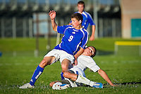 Coeur d'Alene High's Matt Hulquist falls back onto Luke Barrett from Lake City High after passing the ball during the first half of Thursday's 1-1 draw.