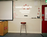 Crew room classroom of the elite 'Red Arrows', Britain's prestigious Royal Air Force aerobatic team at their RAF Scampton, Lincolnshire headquarters. Using two scaled model Hawk jet aircraft he shows how their formation is to be flown on their next training flight. Five autumn and winter months are spent teaching new recruits manual aerobatic display flying while the older members (who rotate positions) learn new disciplines within the routine. Their leaning curve is steep, even for these accomplished fast-jet aviators who had already accumulated 1,500 hours in fighters. By Summer they need every aspect of their 25-minute displays honed to perfection. In this meeting room they meet before and after every flight discussing safety, merits and failures.