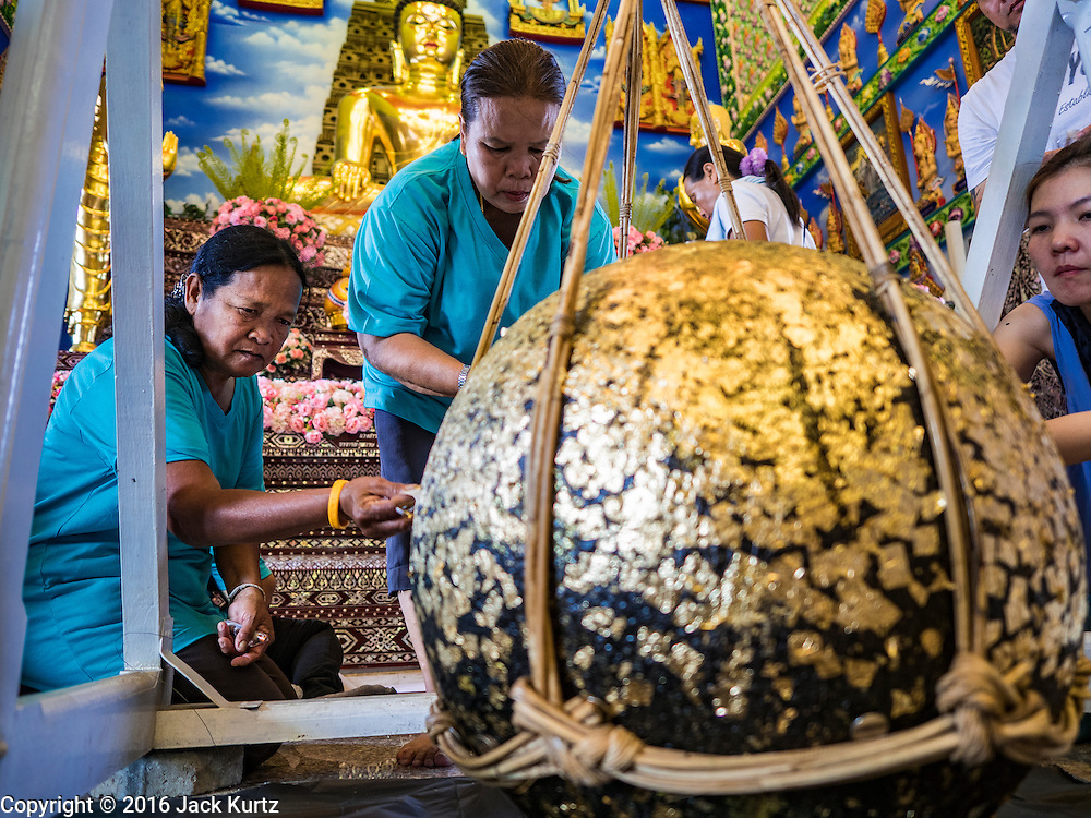 30 JANUARY 2016 - NONTHABURI, NONTHABURI, THAILAND: People make merit by applying gold leaf to a ball in the viharn, or main prayer hall, at Wat Bua Khwan, a large Buddhist temple in Nonthaburi, north of Bangkok, Thailand.        PHOTO BY JACK KURTZ