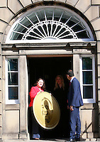 A member of hte Bute House open the door in order to get the delivery.<br /> Scottish Labour deputy leader Anas Sarwar and credit union leader worker Alison Dowling deliver a giant pound coin to Bute House. The First Minister's official residence, to highlight uncertainty over what currency an independent Scotland would use.<br /> <br /> Pako Mera/Universal News And Sport (Europe) 07/08/2014