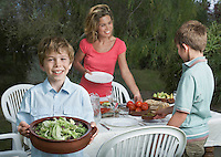 Mother and sons (6-11) preparing dinner table in garden boy holding bowl of salad