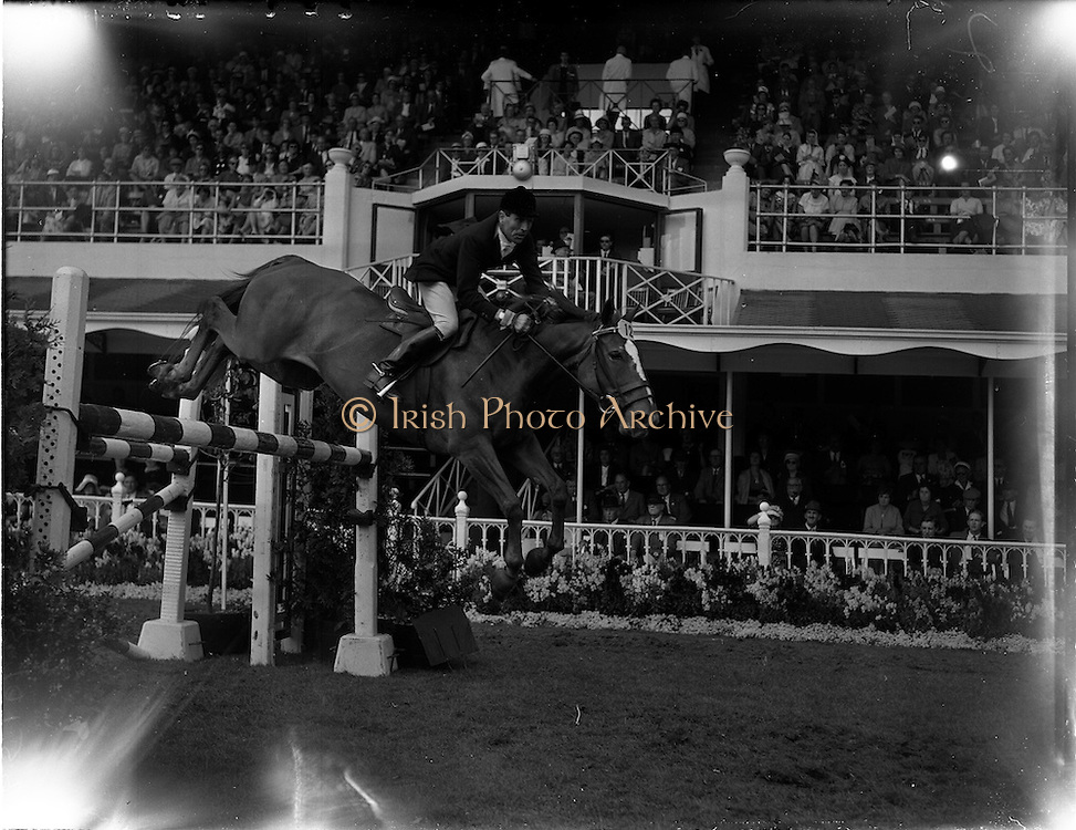 "04/08/1960<br /> 08/04/1960<br /> 04 August 1960<br /> R.D.S Horse Show Dublin (Thursday). Captain the Honourable John Brooke riding ""Tyrenny"" owned by the Honorable Mrs Brooke, clearing a pole jump in the International Jumping Competition for the Boylan Memorial Perpetual Challenge Trophy at the Dublin Horse Show."