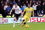 Sheffield Wednesday midfielder Lewis McGugan (37) wins the ball of Derby County defender Craig Forsyth (3) during the Sky Bet Championship match between Derby County and Sheffield Wednesday at the iPro Stadium, Derby, England on 21 February 2015. Photo by Aaron Lupton.