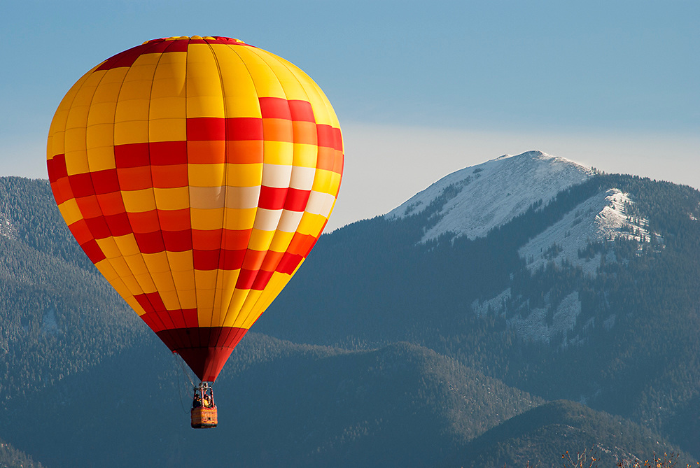 Fine art photograph of a hot air balloon floating in front of Taos mountain, New Mexico. USA.<br />
