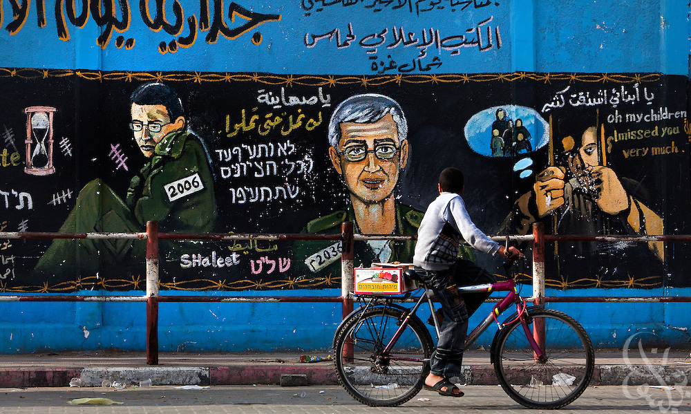 A Palestinian boy rides a bicycle past a HAMAS mural depicting captive Israeli soldier Gilad Shalit December 26, 2009 in the Jabaliyah Refugee Camp in Gaza.  HAMAS and Israel are reported to have been recently negotiating a prisoner exchange that would see some 950 Palestinian prisoners swapped for Shalit, who has been kept captive for more than 3 years now in Gaza.