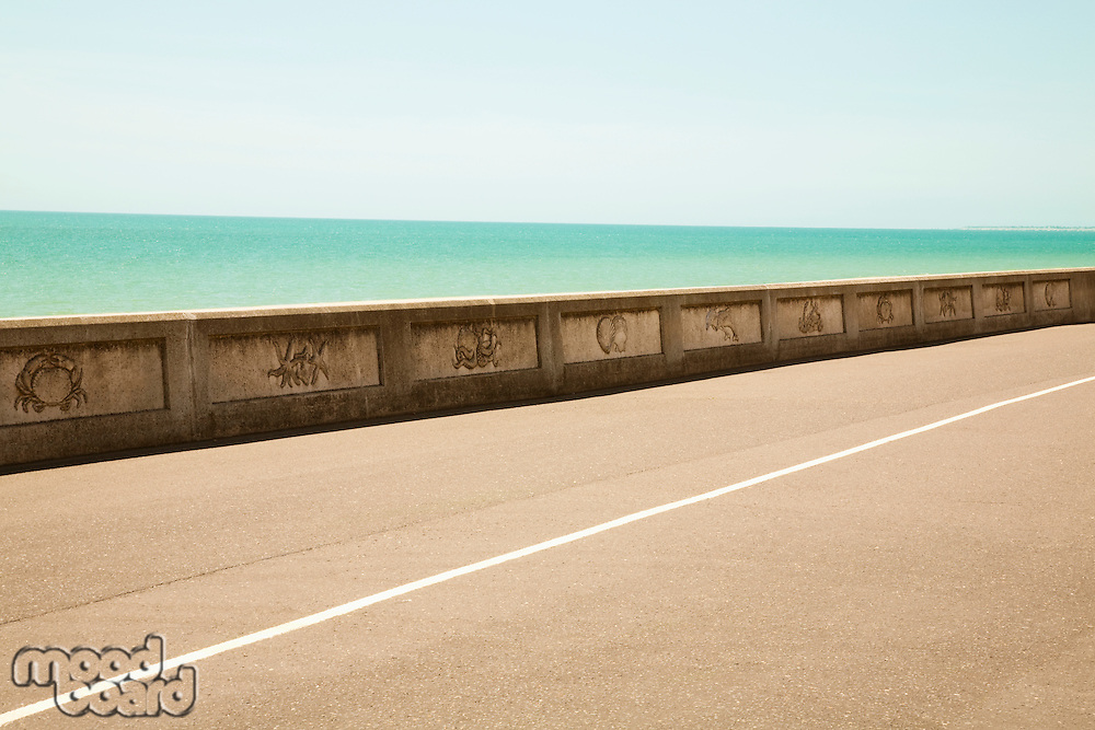 Road by sea wall with turquoise ocean