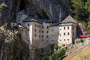 Predjama Castle (Slovene: Predjamski grad or Grad Predjama, Italian: Castel Lueghi) is a Renaissance castle rebuilt within a cave mouth in the historical region of Inner Carniola, south-central Slovenia, Europe. The castle was first mentioned in the year 1274 with the German name Luegg, when the Patriarch of Aquileia built the castle in Gothic style. The present castle was rebuilt in 1570 in Renaissance style by baron Philipp von Cobenzl. It was later acquired and expanded by the Luegg noble family, also known as the Knights of Adelsberg (the German name of Postojna). Predjama village is 11 km from Postojna and 9 km from Postojna Cave.