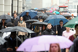 © Licensed to London News Pictures. 08/05/2014<br /> Umbrellas up today in London.<br /> London commuters get wet this morning (08.05.2014) walking across London Bridge,London<br /> Photo credit :Grant Falvey/LNP