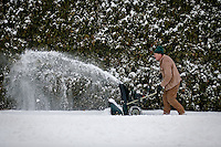 "JEROME A. POLLOS/Press..Ted McCaffree clears a path along the sidewalk Tuesday behind a duplex he owns on 9th Street in Coeur d'Alene. ""It's a lot to clear because it goes behind the house, around the corner and in front of the house,"" McCaffree said during a break. ""Last year I didn't get to work hardly because I was clearing snow every day. This winter isn't so bad."""