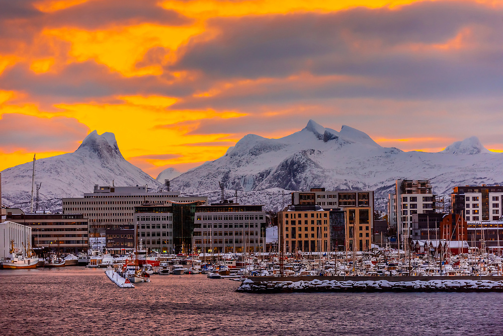 Buildings along the waterfront with snowcapped mountains behind, Bodo, Arctic, Northern Norway.