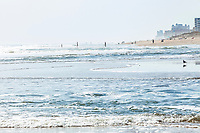 An early morning view down the beach at Ocean City, Maryland showing a number of people out enjoying the beach.
