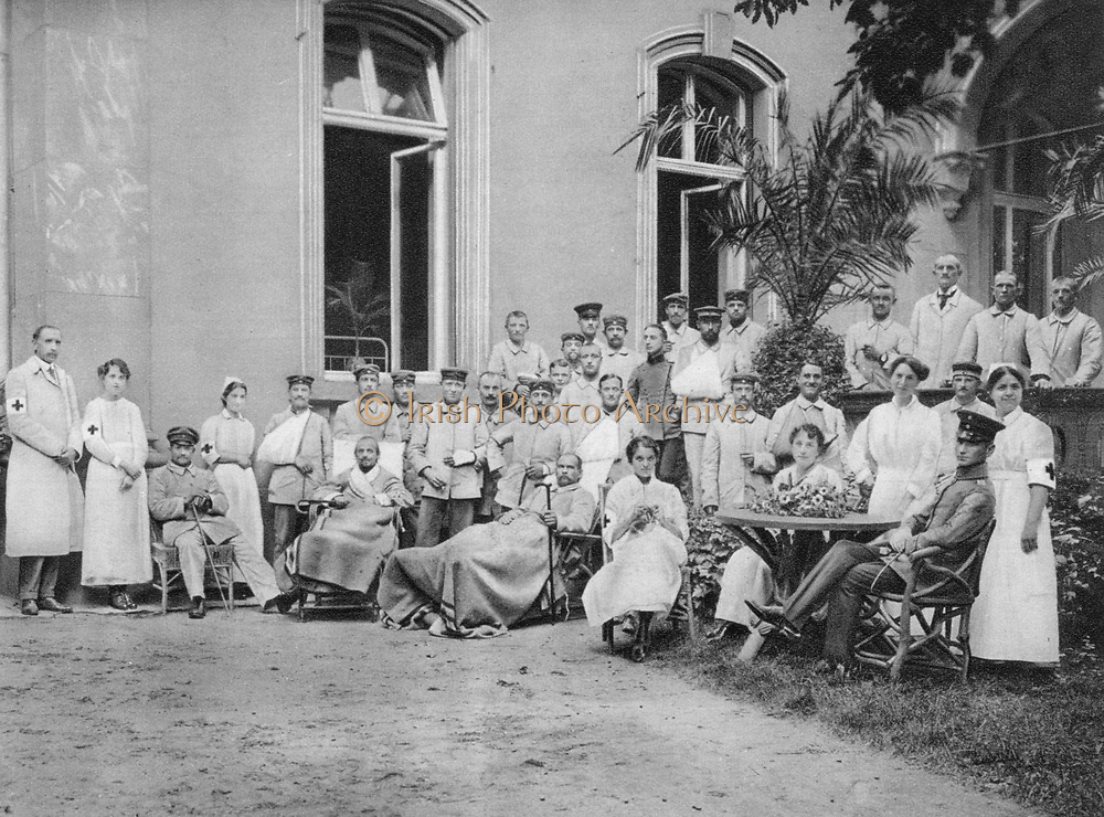 World War I 1914-1918:  Patients and staff grouped outside a house in Frankfort-am-Main converted into a German military hospital, 1915. Army, Medicine, Casualty, Wounded