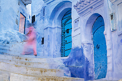 Girl in pink running up blue staircase and walls, Chefchaouen, Morocco
