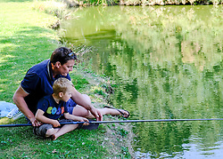A father takes his son fishing for the first time.