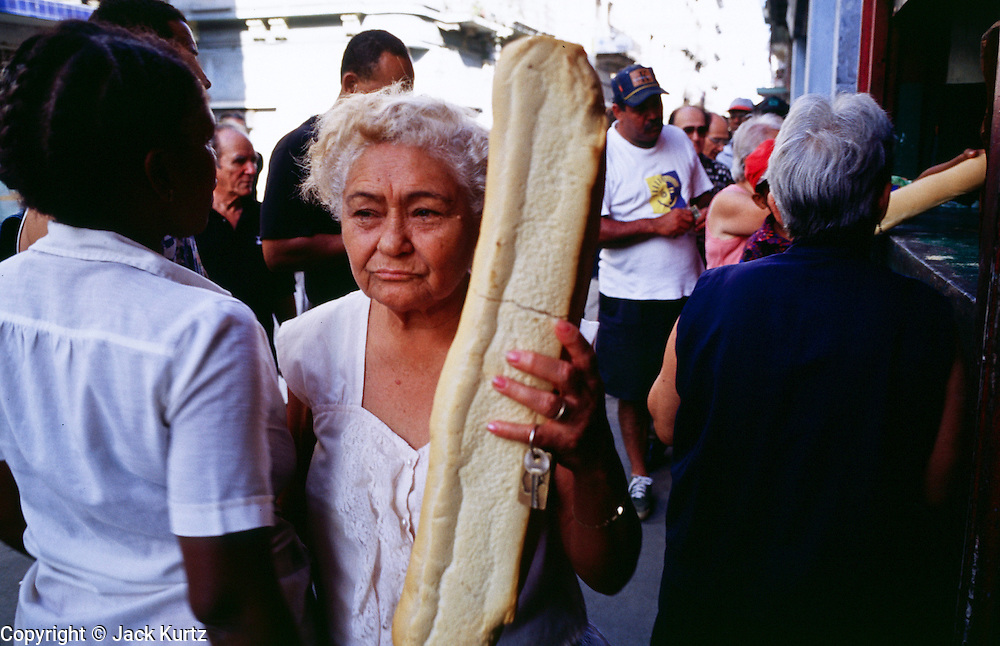 HAVANA, CUBA: A woman walks with her government ration of bread at a government bakery in the central section of Havana, Cuba. Many staples, like bread, rice and meat are still rationed in Cuba. Cubans make up for the lack of government rations by shopping in private farmers? markets and government run dollar stores.  Photo by Jack Kurtz