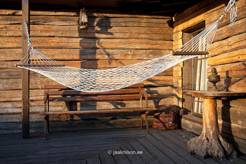 Hammock on cabin porch, Wooden logs, wall.