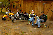 Two women motorcyle riders discuss map while taking a break from riding Harley Davidson motorcycles.