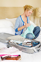 Woman sitting cross-legged on bed next to folded clothes and packed Suitcase
