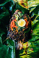 Alleppey, India -- February 19, 2018: Spice-rubbed fish with curry leaves and lemon, grilled in a banana leaf at a small family-run restaurant in the Keralan backwaters.