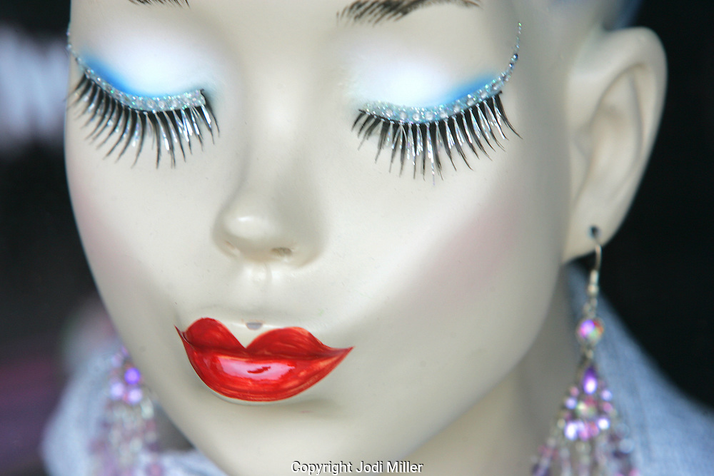Red lipstick and long eyelashes on a mannequin with her eyes closed.