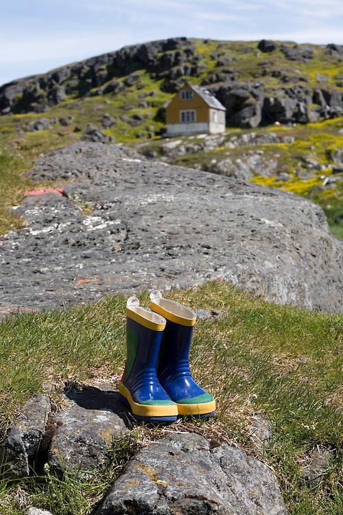 Greenland, Alluitsoq, Child's rubber boots on shoreline at former Moravian settlement of Lichtenau on summer morning.