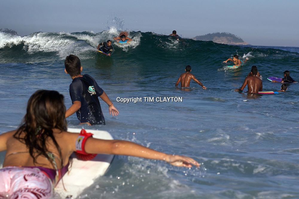 Local youngsters take surf lessons at Sao Conrado beach, Rio de Janeiro,  Brazil. 8th July 2010. Photo Tim Clayton..The beaches of Rio de Janeiro, provide the ultimate playground for locals and tourists alike. Beach activity is in abundance as beach volley ball, football and a hybrid of the two, foot volley, are played day and night along the length and breadth of Rio's beaches. .Volleyball nets and football posts stretch along the cities coastline and are a hive of activity particularly at it's most famous beaches Copacabana and Ipanema. .The warm waters of the Atlantic Ocean provide the ideal conditions for a variety of water sports. Walkways along the edge of the beaches along with exercise stations and cycleways encourage sporting activity, even an outdoor gym is available at the Parque Do Arpoador overlooking the ocean. .On Sunday's the main roads along the beaches of Copacabana, Leblon and Ipanema are closed to traffic bringing out thousands of people of all ages to walk, run, jog, ride, skateboard and cycle more than 10 km of beachside roadway. .This sports mad city is about to become a worldwide sporting focus as they play host to the world's biggest sporting events with Brazil hosting the next Fifa World Cup in 2014 and Rio de Janeiro hosting the Olympic Games in 2016...