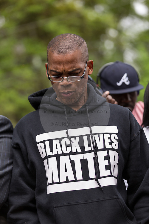 An activist prays during a peace vigil at the spot where unarmed motorist Walter Scott was gunned down by police April 12, 2015 in North Charleston, South Carolina. About 100 people showed up for the brief vigil following a healing service at Charity Mission Baptist Church.
