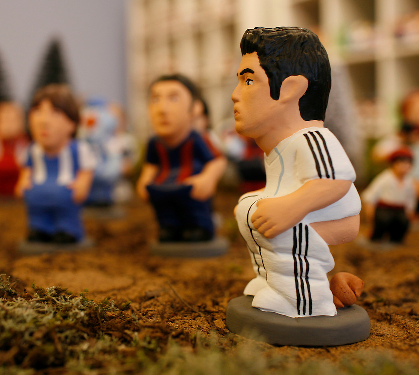 "Torroella de Mongri, Spain, 19 November 2009. .A company in Torroella de Montgrí (Girona, Spain) called ""caganer.com"" specialized in the production of ""caganers"" unveiled today  the new figures for Christmas as Real Madrid player, Cristiano Ronaldo..A ""Caganer"" is a small figure from Catalonia, usually made of fired clay,  and depicted as squating person in the act defecating. .""Caganer"" is Catalan for pooper. It fomrs part of one of the typical figures of  the manger or ""Nativity"" scene together with Mary, .Joseph and the baby Jesus but hidden in a corner. It is a humorous figure, originally portraying a peasant wearing a .barretina (a red stocking hat), and seems to date from the 18th century when it  was believed that the figure's depositions  .would fertilize the earth to bring a properous year. With  the course of the time, the original  personage of this pooping figure .was  substituted with personalities from the political and sports world and other famous personalities."
