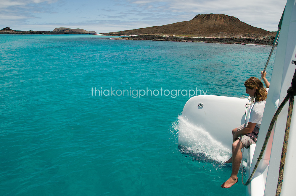 A twenty-something man rides on the bow/trampoline of a catamaran boat in the Galapagos Islands.