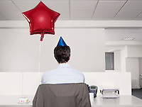 Man celebrating birthday working alone in office
