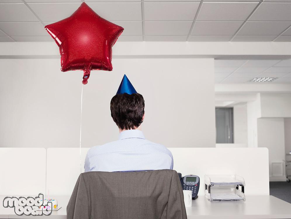 Man celebrating birthday working alone in office