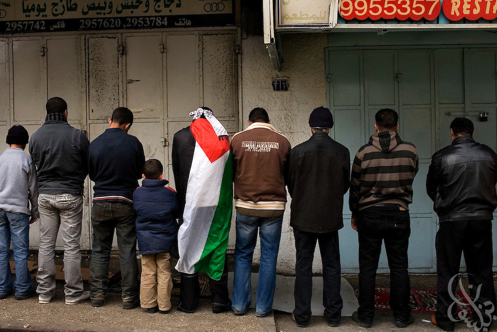 Palestinian men gather for Friday Prayers prior to a protest against the ongoing Israeli incursion into Gaza January 09, 2009 in the West Bank City of Ramallah. Scuffles broke out during the protest of more than 10,000 marchers between supporters of Fatah, and Hamas.