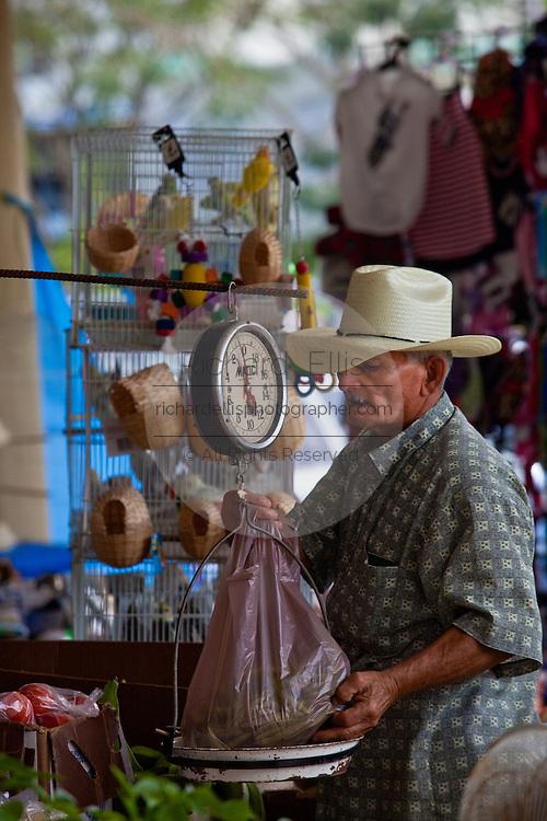 A farmer weighs a purchase at the Friday bazaar in San Sebastian, Puerto Rico. (photo by Charleston SC photographer Richard Ellis)