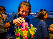"03 NOVEMBER 2017 - BANGKOK, THAILAND: A girl lights incense in her krathong before floating it during Loi Krathong at Wat Prayurawongsawat on the Thonburi side of the Chao Phraya River. Loi Krathong is translated as ""to float (Loi) a basket (Krathong)"", and comes from the tradition of making krathong or buoyant, decorated baskets, which are then floated on a river to make merit. On the night of the full moon of the 12th lunar month (usually November), Thais launch their krathong on a river, canal or a pond, making a wish as they do so. Loi Krathong is also celebrated in other Theravada Buddhist countries like Myanmar, where it is called the Tazaungdaing Festival, and Cambodia, where it is called Bon Om Tuk.     PHOTO BY JACK KURTZ"