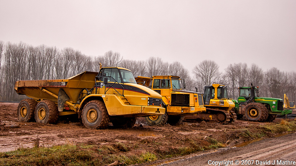 Some Cat's (and a John Deere) parked in the mud on a misty winter day. There used to be trees here, soon to become a housing tract. Image taken with a Nikon D2xs camera and a new 12-24 mm f/4 DX lens (ISO 100, 24 mm, f/4, 1/200 sec).