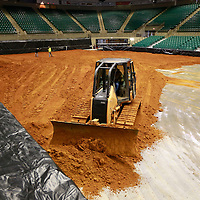 Thomas Wells | BUY AT PHOTOS.DJOURNAL.COM<br /> Paul Smithey begins spreading dirt over the floor of the BancorpSouth Arena on Wednesday as he helps get the facility ready for this weekends rodeo.