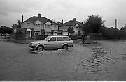 "Flooding at the Dodder..1986..26.08.1986..08.26.1986..28th August 1986..As a result of Hurricane Charly (Charlie) heavy overnight rainfall was the cause of severe flooding in the Donnybrook/Ballsbridge areas of Dublin. In a period of just 12 hours it was stated that 8 inches of rain had fallen. The Dodder,long regarded as a ""Flashy"" river, burst its banks and caused great hardship to families in the 300 or so homes which were flooded. Council workers and the Fire Brigades did their best to try and alleviate some of the problems by removing debris and pumping out some of the homes affected..Note: ""Flashy"" is a term given to a river which is prone to flooding as a result of heavy or sustained rainfall...Photograph of motorists trying to avoid the worst of the flooding by driving on the 'wrong' side of the road. Motorists were advised to be vigilant as manhole covers had been displaced by the water pressure and were lying unseen underwater."