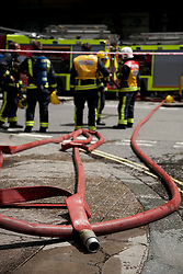 © Licensed to London News Pictures. LONDON, UK  14/06/11. Hoses litter the ground as a fire crew deals with a building on fire on Aldwich in London today (Tuesday) as members of the public watch on and take pictures. Please see special instructions for usage rates. Photo credit should read Matt Cetti-Roberts/LNP