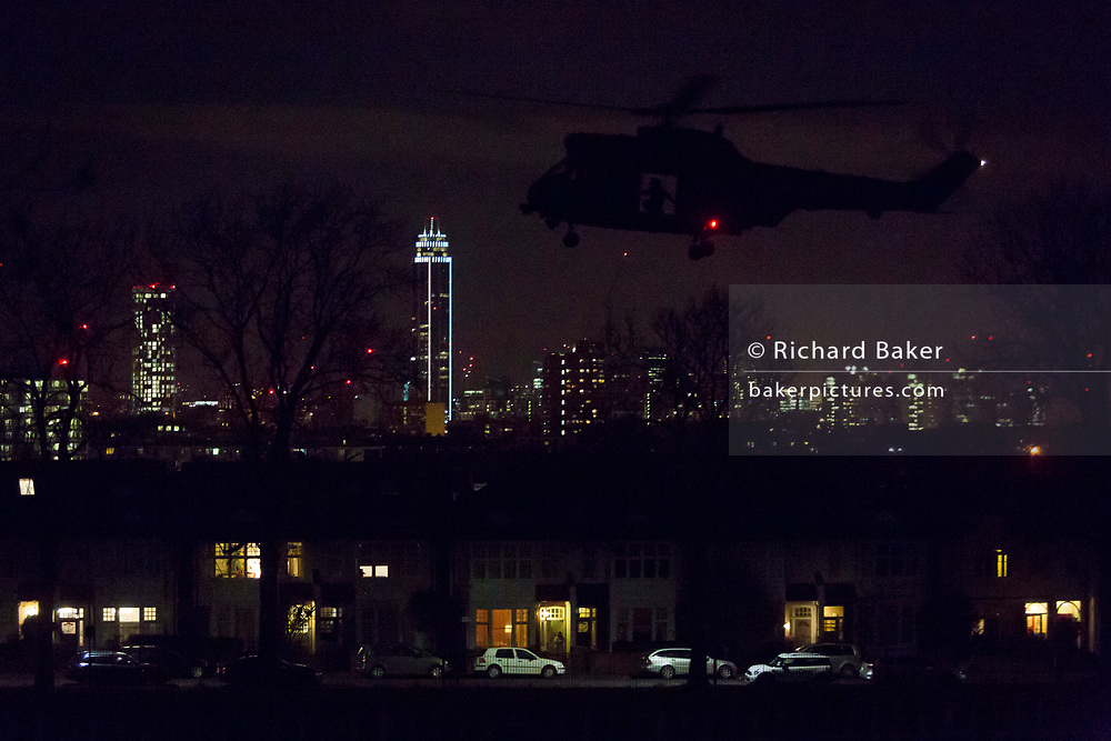 A Puma helicopter (one of a pair) takes-off from Ruskin Park at 10.50pm, on 7th March 2017, in the London borough of Lambeth, England. Pumas in ones or twos occasionally land for a few minutes with engines running before departing again for other destinations. It's believed these landings help train flight crews for future evacuation of VIPs in times of emergency using open space locations like public parks. On this occasion, the two aircraft landed with lights off (so perhaps using night-vision) in the darkness.