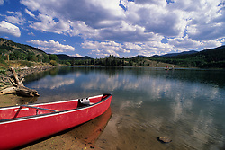 Stock photo of a canoe pulled up onto the shore of a remote lake