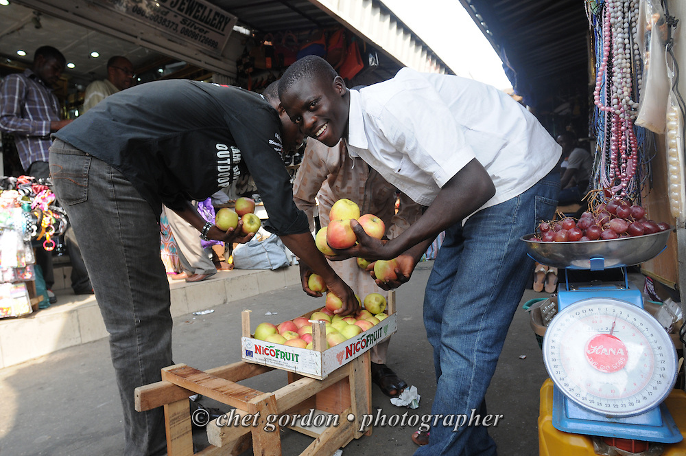 Young Nigerian men sort apples at the Wuse Market in Abuja, Nigeria on Saturday, December 8, 2012.
