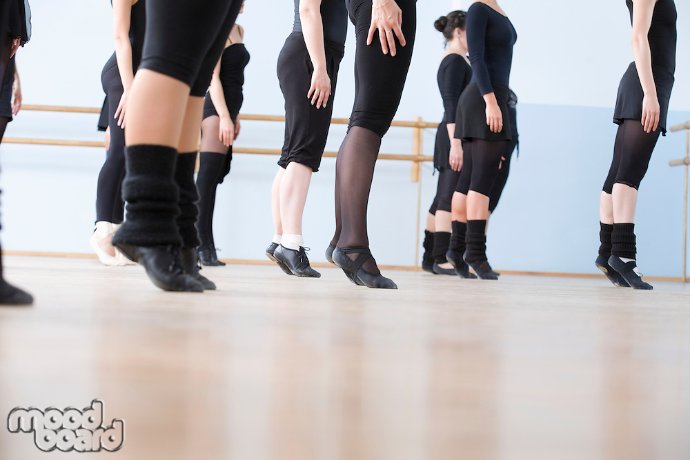 Young women practise ballet in a rehearsal room