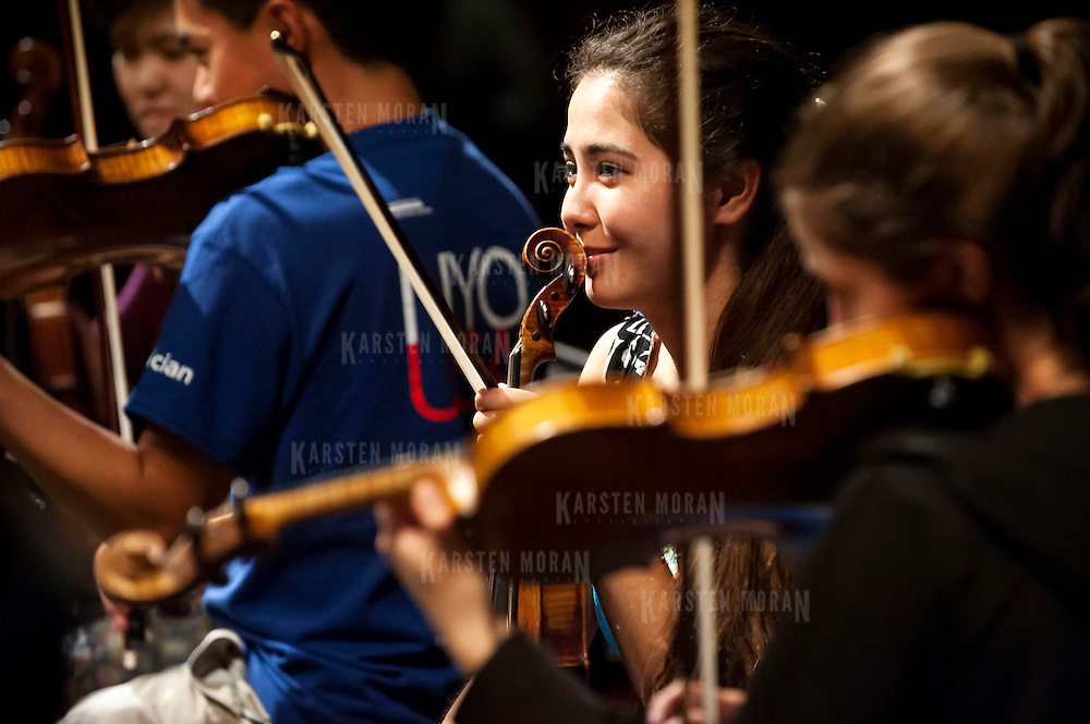 July 9, 2013 - Purchase, NY : Members of the National Youth Orchestra of the United States of America, including Julia Popham, center, get ready for rehearsal with conductor Valery Gergiev (not pictured) at SUNY Purchase's Performing Arts Center in Westchester on Tuesday afternoon. The Orchestra, a new project of Carnegie Hall's Weill Music Institute, is comprised of musicians aged 16-19, hand-picked from across the country. The program -- and orchestra -- will kick off its inaugural season with a performance at SUNY Purchase on Thursday evening, and then head off to perform in Washington DC,  Moscow, St. Petersburg, and London. Popham is from Golden, Colo. CREDIT: Karsten Moran for The New York Times